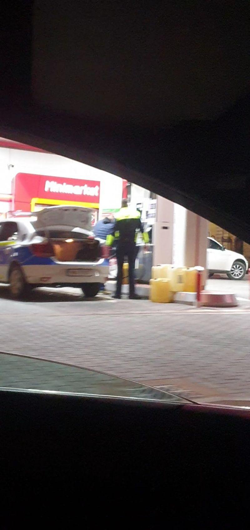 FOTO: SIGHETU MARMAȚIEI - Un polițist umple mai multe canistre cu combustibil în portbagajul unei autospeciale